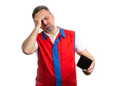 Male hypermarket or supermarket employee touching forehead with hand as worried gesture while holding empty wallet isolated on white Reklamní fotografie