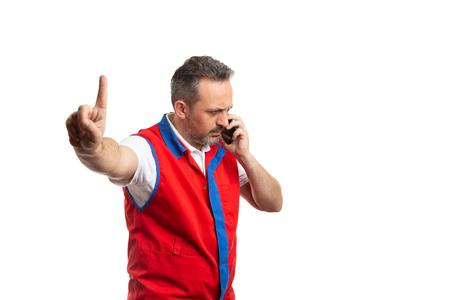 Empleado de supermercado masculino enfocado haciendo gesto de espera con el dedo índice mientras habla por teléfono gesto aislado sobre fondo blanco. Foto de archivo