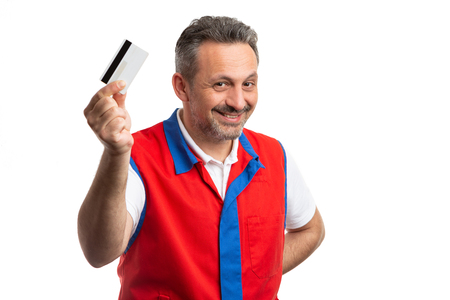 Smiling male hypermarket or supermarket employee presenting credit card isolated on white background