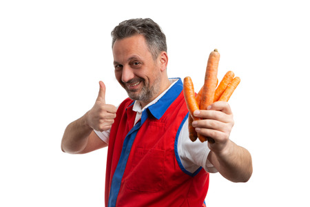 Trustworthy grocery store or hypermarket male employee making like gesture with thumb up as presenting carrots isolated on white