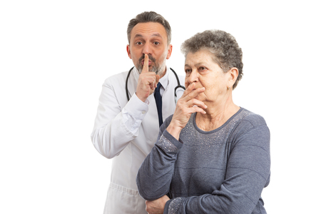 Male doctor making shush gesture by holding index finger up behind suspicious elderly patient isolated on white background