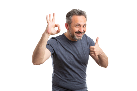 Happy man holding fingers as okay and thumb up like gesture wearing grey t-shirt as casual clothing concept isolated on white Stock fotó