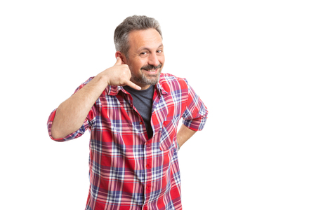 Friendly man smiling while making call me gesture by holding fingers as phone near ear isolated on white background Reklamní fotografie