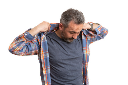 Man getting ready and arranging collar of blue and orange plaid shirt with hands isolated on white studio background