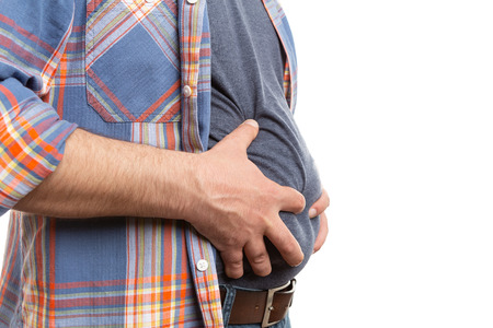 Closeup of man touching bloated stomach with copyspace as abdomen pain concept isolated on white studio background