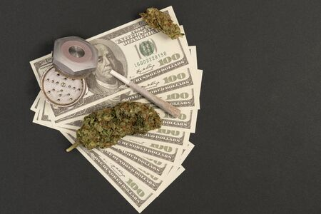 Closeup of grinder and dollar bill with benjamin franklin smokeing rolled joint isolated on black studio background
