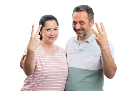 Smiling couple showing two and three numbers with fingers as counting concept isolated on white background Banco de Imagens