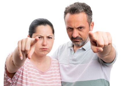 Angry man and woman couple pointing index fingers at camera as looking concept closeup isolated on white background