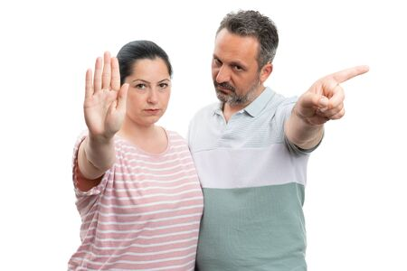 Unhappy man and woman couple making stop gesture with palm or index finger as forbidden concept isolated on white
