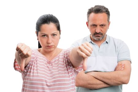 Angry woman making double thumbs-down dislike gesture and man with crossed arms behind as couple concept isolated on white