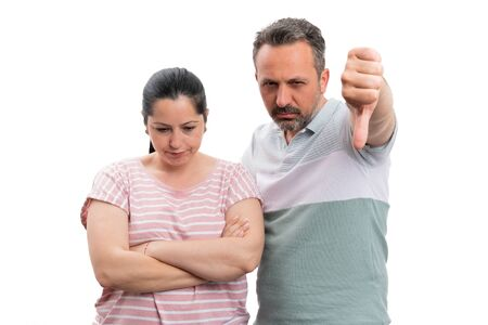 Man showing thumb-down as dislike gesture to upset woman with crossed arms isolated on white background Stock Photo