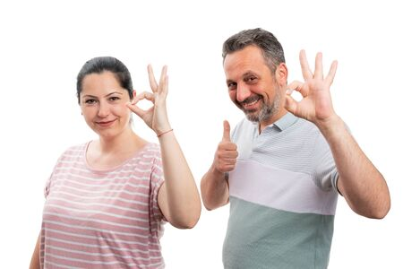 Cheerful couple making thumb up like and okay gesture with fingers isolated on white studio background Stock Photo