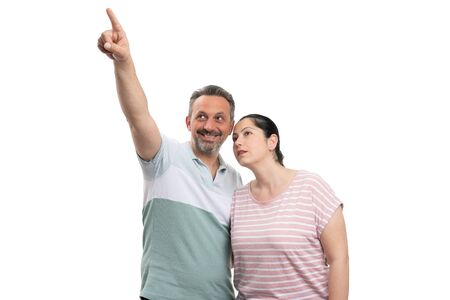 Smiling pointing index finger at above corner and woman looking with curious expression as couple concept isolated on white Stock Photo