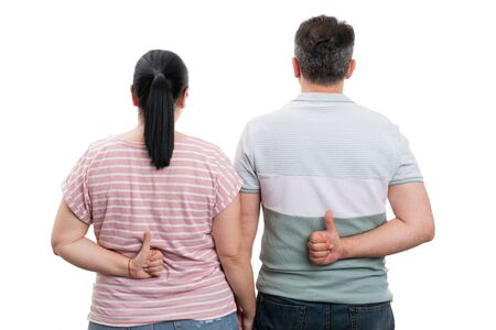 Couple holding thumbs up as like gesture behind back isolated on white studio background Stock Photo