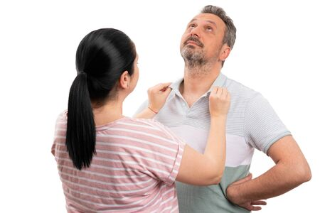 Woman arranging polo shirt collar of man as couple getting ready concept isolated on white background