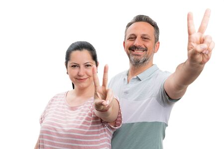 Smiling couple making peace or victory sign with index and middle fingers isolated on white studio background Stock Photo