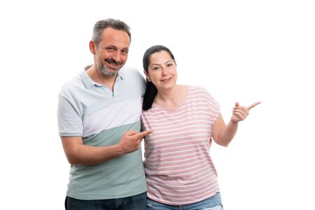 Smiling man and woman couple pointing at blank copyspace for advertising with index fingers isolated on white Stock Photo