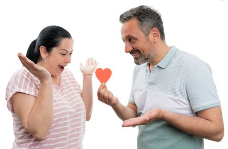 Joyful man gifting red paper heart to smiling woman as love and relationship concept isolated on white background