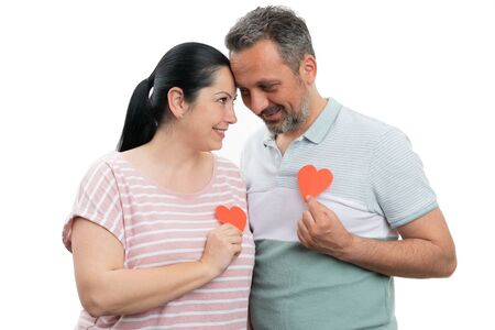 Loving man and woman couple holding red paper hearts over chest as romantic concept isolated on white studio background Stock Photo