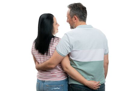 Happy man and woman hugging and looking at each other with back to camera isolated on white background