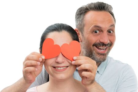 Cheerful man holding red paper hearts over woman eyes as in love concept isolated on white background Stock Photo