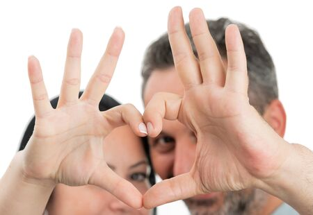Closeup of heart gesture made with fingers by man and woman couple as relationship concept isolated on white