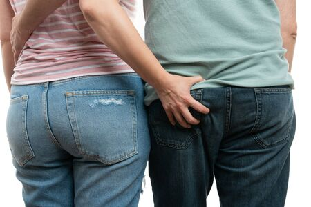 Closeup of woman touching man butt wearing jeans as couple concept isolated on white background