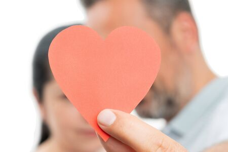 Closeup of couple holding red paper heart as romantic concept isolated on white studio background Stock Photo