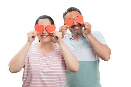 Smiling man and woman covering eyes with red paper hearts as in love couple concept isolated on white background