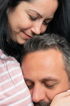 Closeup of loving woman hugging man as couple cuddling concept isolated on white studio background Stock Photo