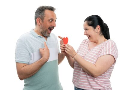 Happy woman gifting red paper heart to man making surprised expression and pointing index fingers to himself isolated on white