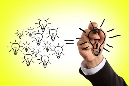Closeup of man wearing suit drawing lightbulb using black marker as idea concept on invisible screen with yellow background