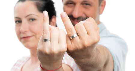 Closeup of man and woman couple presenting wedding rings on fingers isolated on white studio background Stock Photo