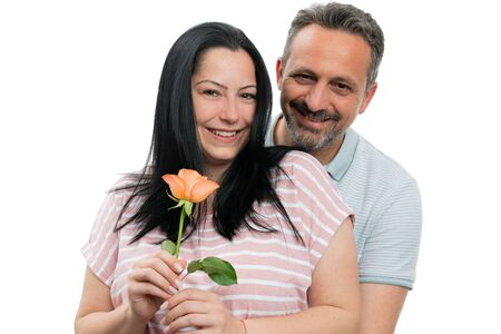 Cheerful man and woman couple hugging with orange rose as gift isolated on white studio background