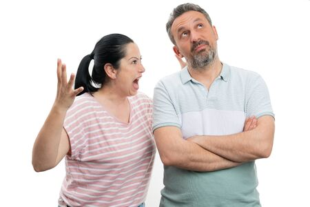 Angry woman yelling at man with careless expression and crossed arms isolated on white studio background