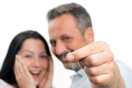 Closeup of engagement ring with diamond presented by man and woman couple isolated on white background Stock Photo