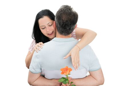 Happy woman reaching with hand at orange rose hidden behind man back as couple concept isolated on white Stock Photo