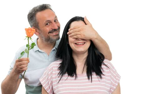 Smiling man covering woman eyes with hands for giving orange rose gift isolated on white studio background Stock Photo