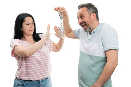 Smiling man showing handcuffs to woman making refusing gesture and expression isolated on white studio background