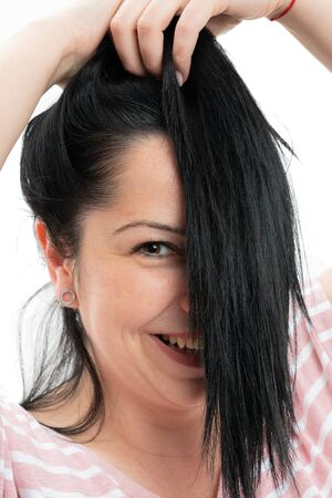 Portrait of happy woman covering half face with dark hair closeup isolated on white studio background