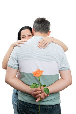 Man and woman couple hugging with man hiding orange rose behind back isolated on white background Stock Photo