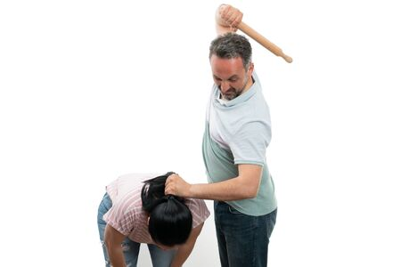 Aggressive man preparing to hit scared woman with rolling pin while grabbing her hair isolated on white Stock Photo