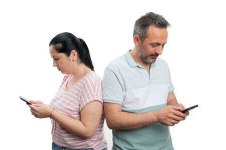 Man and woman couple looking at phones and texting with serious expression isolated on white background Stock Photo