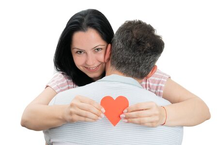 Couple hugging and smiling female holding red paper heart shape as romantic concept isolated on white background Stock Photo