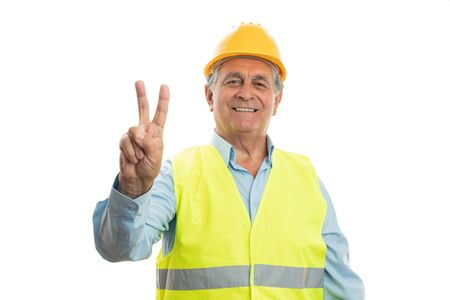 Old male builder showing victory or peace sign with index and middle fingers isolated on white