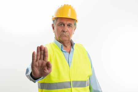 Old builder man angry as making forbidden gesture with index finger isolated on white studio background