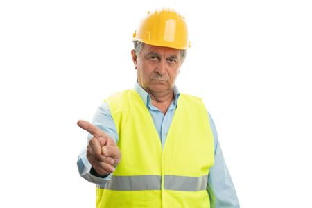 Old builder man with serious expression pointing at blank copyspace above isolated on white background