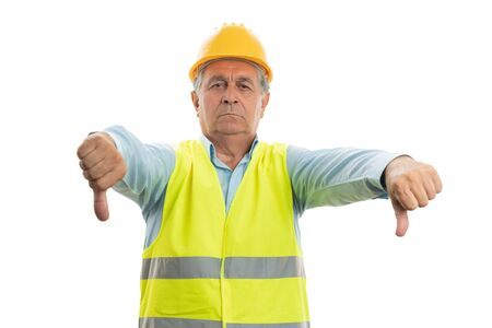 Builder man with upset expression showing double dislike gesture using thumbs isolated on white background 写真素材