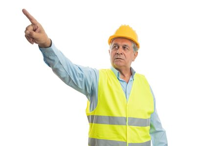 Old builder man with angry expression pointing index finger at camera isolated on white studio background 写真素材