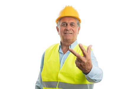 Friendly male old builder showing number two with fingers as counting concept isolated on white background 写真素材